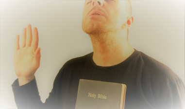 man makes a prayer with the Bible and with his hand raised