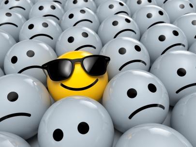 Happy Smiley Emoticon mit Sonnenbrillen zwischen traurigen Emoticons