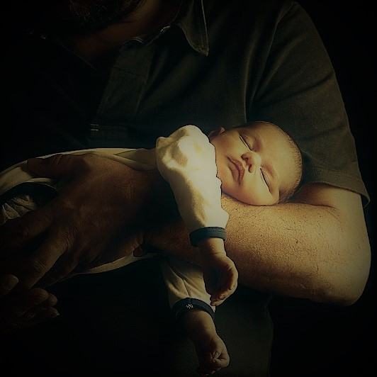Newborn baby and his father's hand