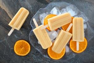 Homemade orange yogurt popsicles in an ice filled bowl