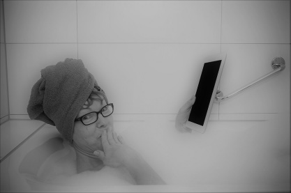 Confused woman in bathtub with tablet computers