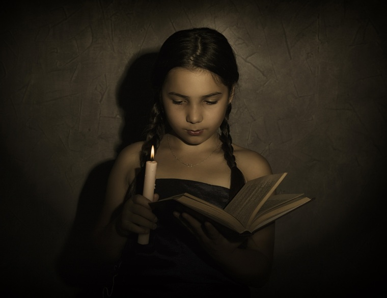 little girl reading book and studying in candle light in dark room