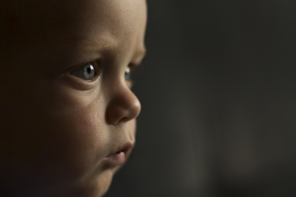 Portrait of serious one year toddler on the dark background. Close-up view. Copy space