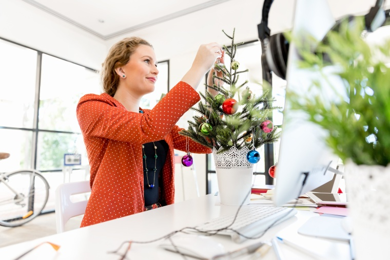 Young woman in office with christmas tree