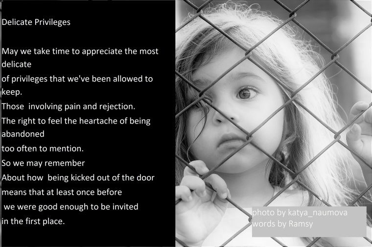 Toned portrait of Sad little girl looks through wire fence