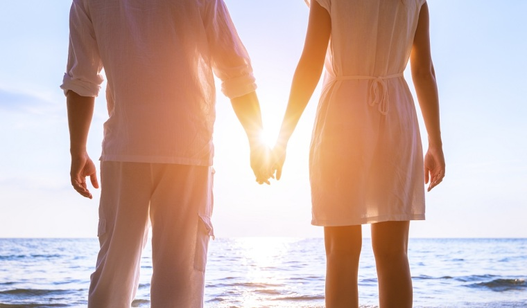 Beautiful romantic couple in white clothes holding hands at beach