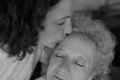 Adult daughter kissing elderly mother