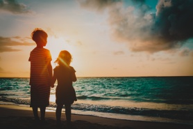 happy little boy and girl holding hands at sunset