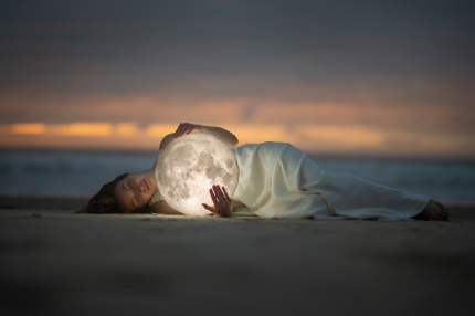 Astrology. Secret and riddle. Beautiful attractive girl on a night beach with sand hugs the moon, art photo.