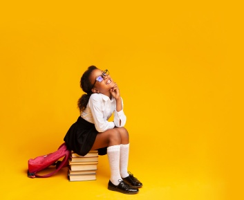 Elementary School Girl Dreaming Sitting On Stack Of Books