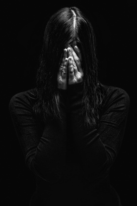 Emotional woman crying and covering the face with the hands hiding the tears, on a black or dark background. Concept for victim, depression, pain, grief, mourn, despair, sadness, fear.