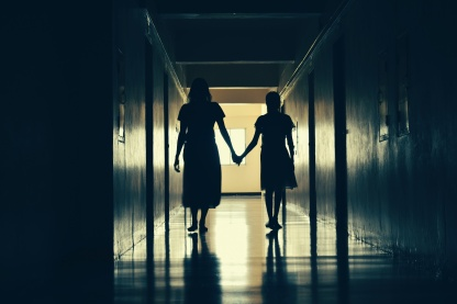 Silhouettes of people in a long dark corridor. The ghosts of a woman and child. Dark creepy hallway with ghosts.