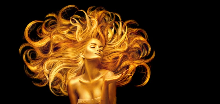 Golden beauty woman. Sexy model girl with golden makeup and long hair pointing hand over black. Metallic gold glowing skin and fluttering hair