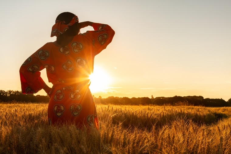 African woman in traditional clothes standing in a field of crops at sunset or sunrise
