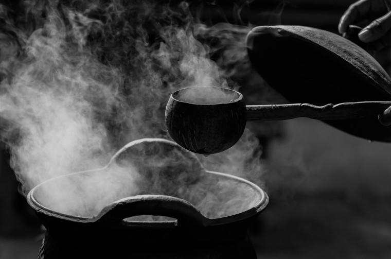 Handle spoon dipper over the smoke from traditional clay hot pot
