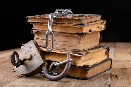 Old books bound by a new shiny chain with an old padlock. Forbidden old works artists on a wooden table.