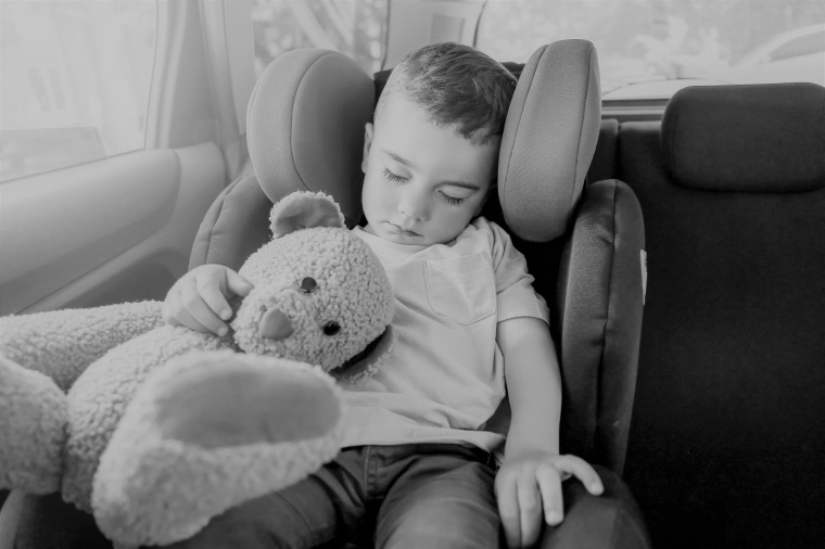 Baby boy sleeping on car safety seat